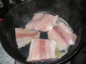 Жарит рыбу